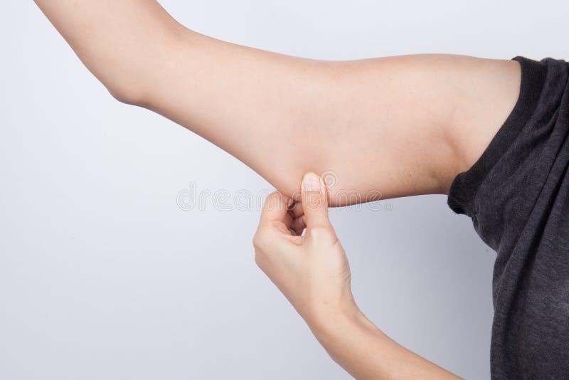 Junge Frau, die ihr Armfett überprüft lizenzfreies stockbild
