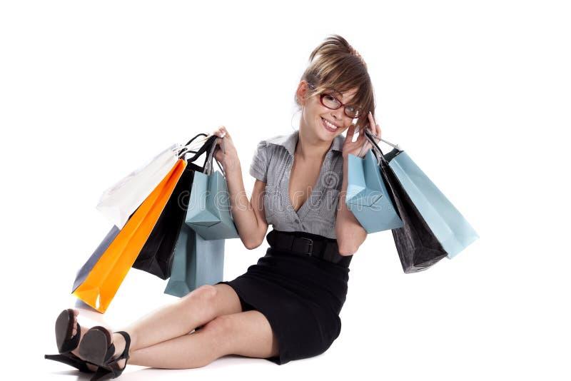 Junge Frau, die ihr Einkaufen bewundert stockfotografie