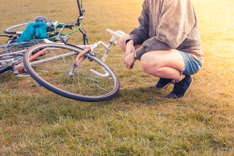 Junge Frau, die ihr Fahrrad im Park betrachtet stockbild