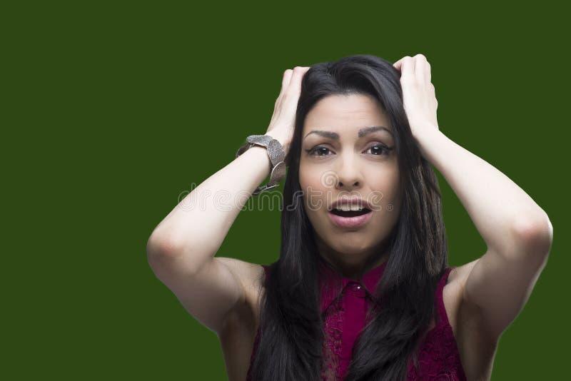 Junge Frau, die ihr Furcht in Richtung zu jemand über einem grünen Schirm zeigt, der durch jeden möglichen Hintergrund ersetzt we stockbilder