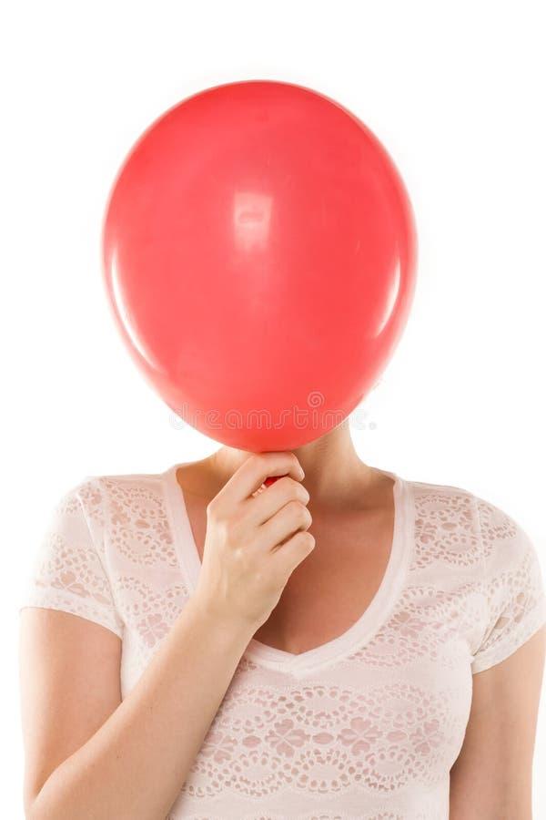 Junge Frau, die ihr Gesicht hinter Ballon versteckt stockfotos
