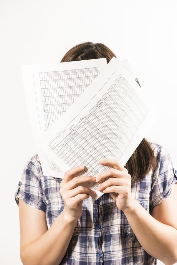 Junge Frau, die ihr Gesicht hinter Blättern Papier versteckt lizenzfreie stockfotos