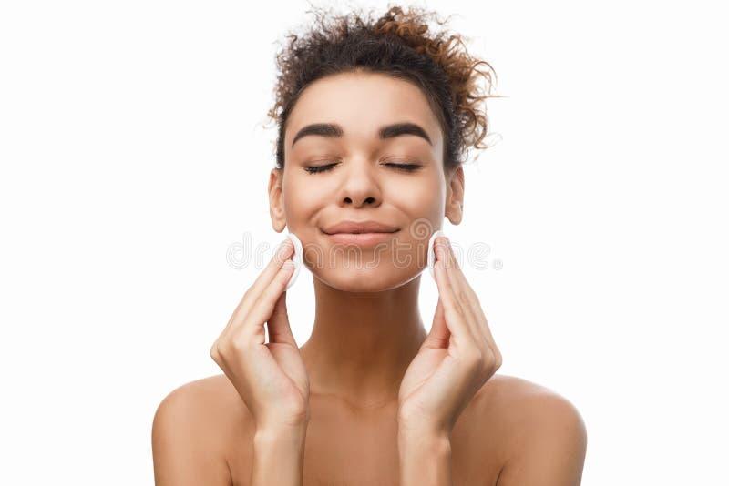 Junge Frau, die ihr Gesicht mit Baumwollauflagen säubert stockfotos