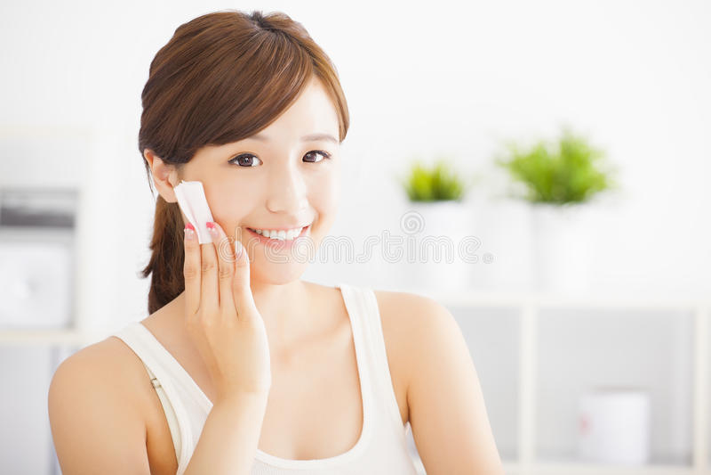 junge Frau, die ihr Gesicht mit Baumwolle säubert stockbilder
