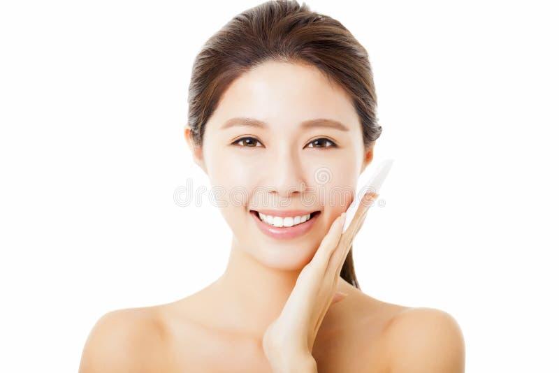 junge Frau, die ihr Gesicht mit Baumwolle säubert stockbild