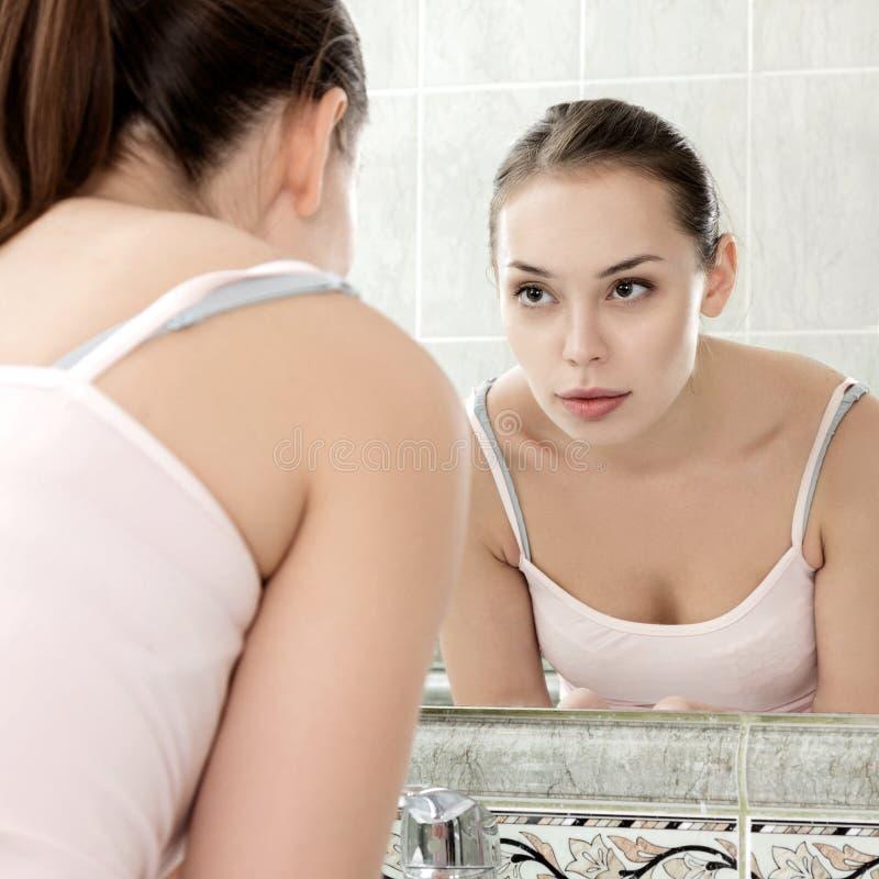 Junge Frau, die ihr Gesicht mit Trinkwasser wäscht lizenzfreies stockbild