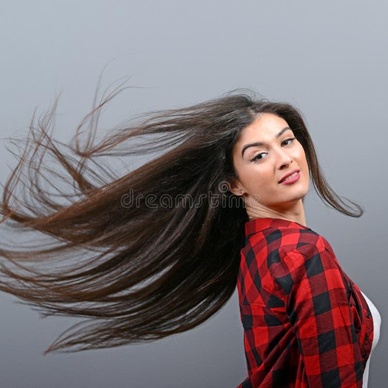 Junge Frau, die ihr Haar schlägt und gegen grauen Hintergrund aufwirft stockfotografie