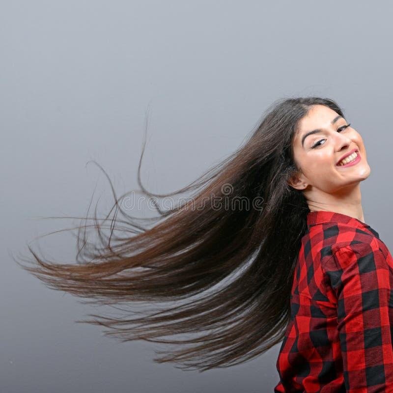 Junge Frau, die ihr Haar schlägt und gegen grauen Hintergrund aufwirft lizenzfreies stockbild