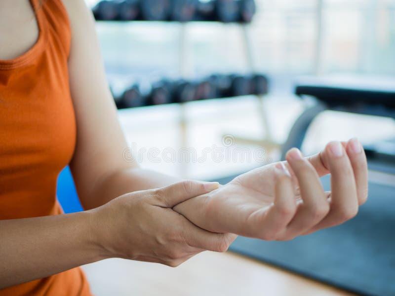 Junge Frau, die ihr Handgelenk nachdem dem Ausarbeiten massiert lizenzfreies stockfoto