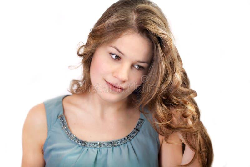 Junge Frau, die ihr langes Haar betrachtet stockfotos