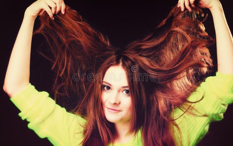 Junge Frau, die ihr langes Haar zieht stockfoto