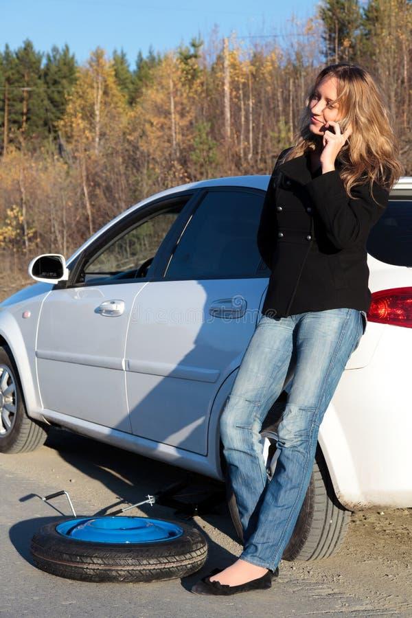 Junge Frau, die ihr schädigendes Auto bereitsteht stockfotografie