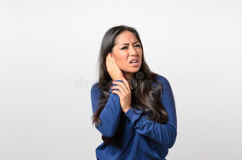 Junge Frau, die ihr schmerzliches Ohr hält lizenzfreies stockbild