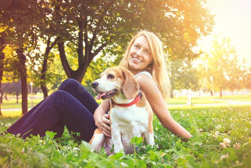 Junge Frau, die ihr Spürhundhündchen im Park umfasst lizenzfreies stockbild