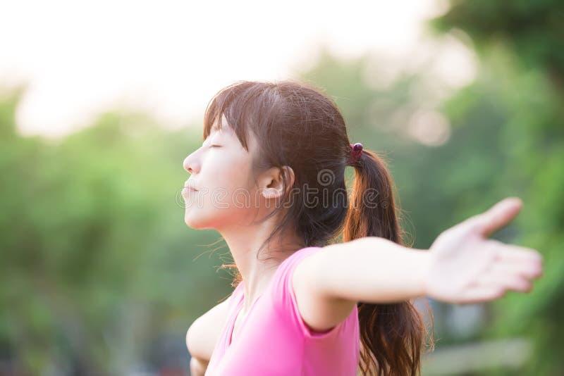 Junge Frau, die ihre Arme anhebt lizenzfreies stockfoto