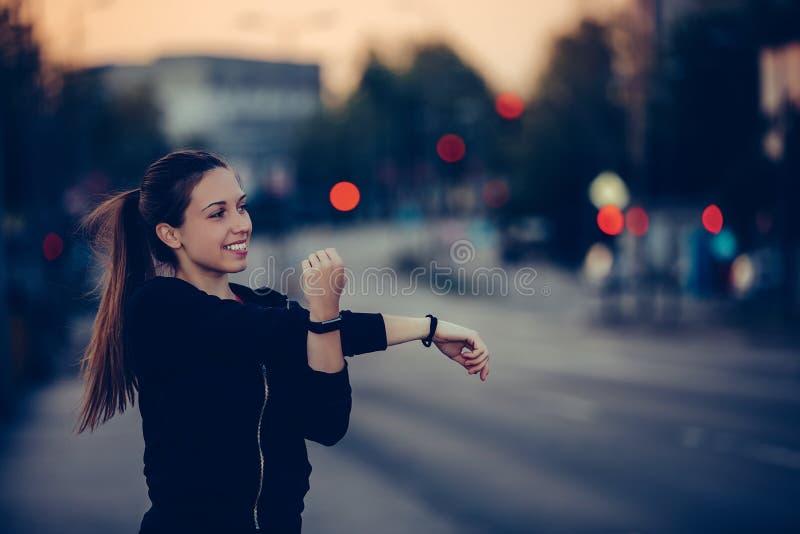 Junge Frau, die ihre Arme in der Stadt, nachts ausdehnt lizenzfreie stockfotos