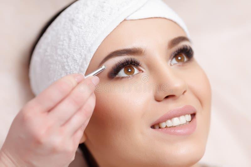 Junge Frau, die ihre Augenbrauen im Schönheitssaal auszupft stockfotos