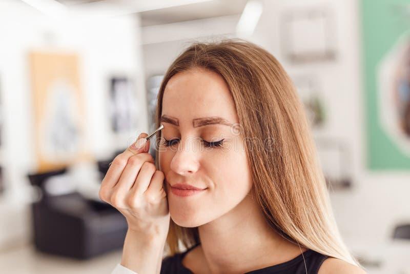 Junge Frau, die ihre Augenbrauen im Schönheitssaal auszupft stockbilder