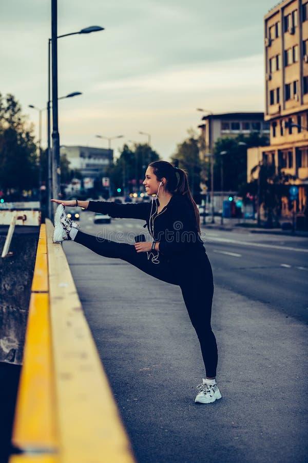 Junge Frau, die ihre Beine auf Flussbrücke, nachts ausdehnt lizenzfreies stockfoto