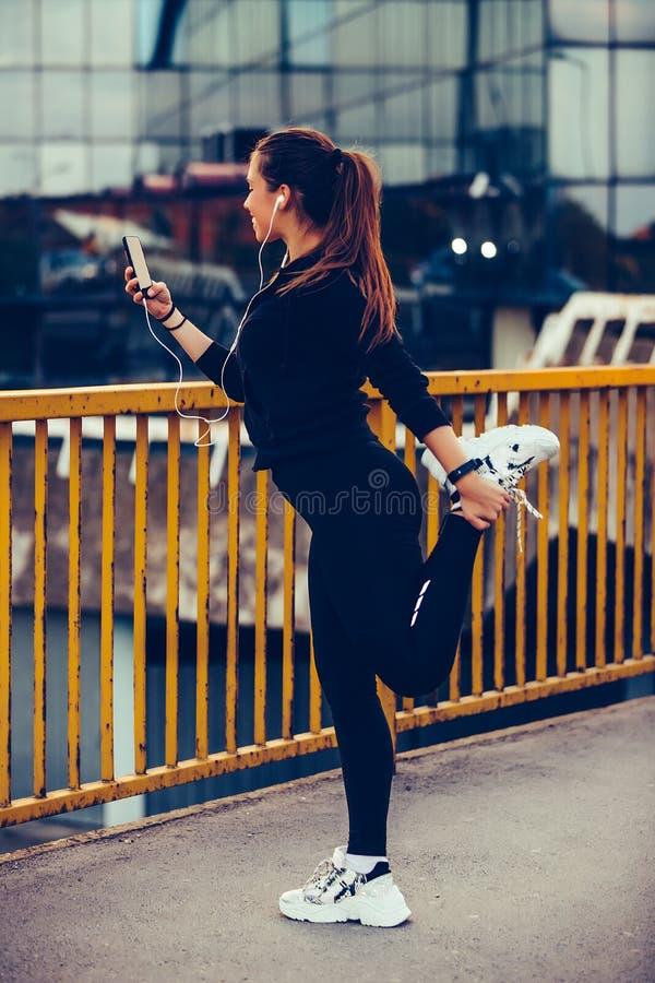 Junge Frau, die ihre Beine nachdem dem Rütteln ausdehnt lizenzfreie stockfotografie
