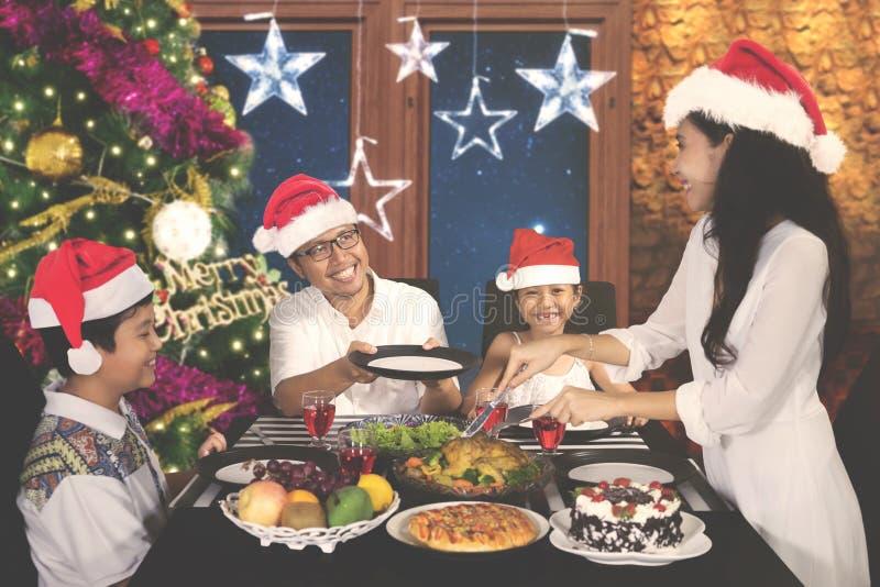 Junge Frau, die ihre Familie am Weihnachtsessen dient stockfoto