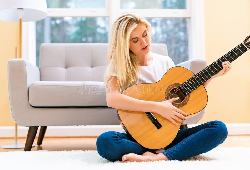 Junge Frau, die ihre Gitarre spielt stockfotografie
