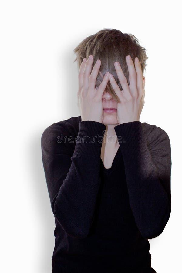 Junge Frau, die ihre Hände über ihrem Gesicht hält stockbild