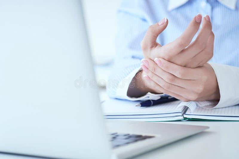 Junge Frau, die ihre wunde Hand auf Handgelenknahaufnahme hält Schmerz von der Anwendung des Computers Bürosyndrom-Handschmerz du stockfotografie