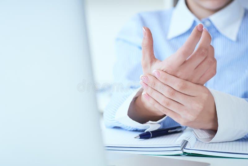 Junge Frau, die ihre wunde Handgelenknahaufnahme hält Schmerz von der Anwendung des Computers B?rosyndrom-Handschmerz durch Beruf stockbild