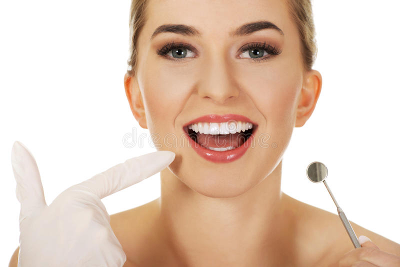Junge Frau, die ihre Zähne überprüft stockfoto