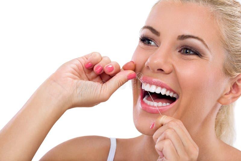 Junge Frau, die ihre Zähne flossing ist lizenzfreie stockfotos