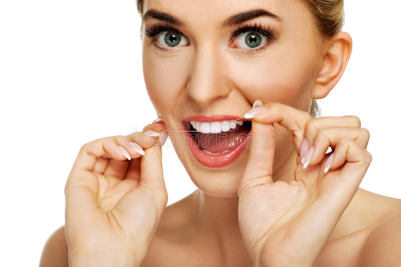 Junge Frau, die ihre Zähne flossing ist stockfoto