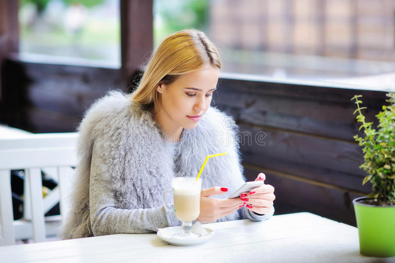 Junge Frau, die ihre Zeit während der Kaffeepause genießt lizenzfreies stockfoto