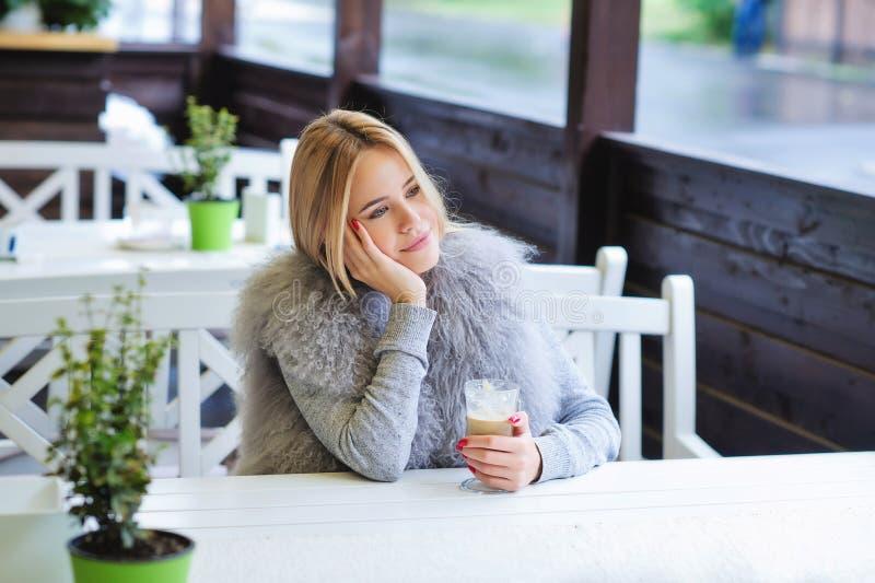 Junge Frau, die ihre Zeit während der Kaffeepause genießt stockbild