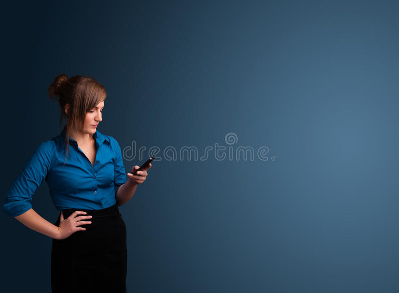 Junge Frau, die an ihrem Telefon mit Kopienraum steht und schreibt lizenzfreie stockfotografie