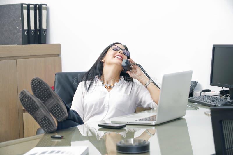 Junge Frau, die an ihrem Tisch mit den Beinen auf dem Schreibtisch spricht am Handy sitzt stockfoto