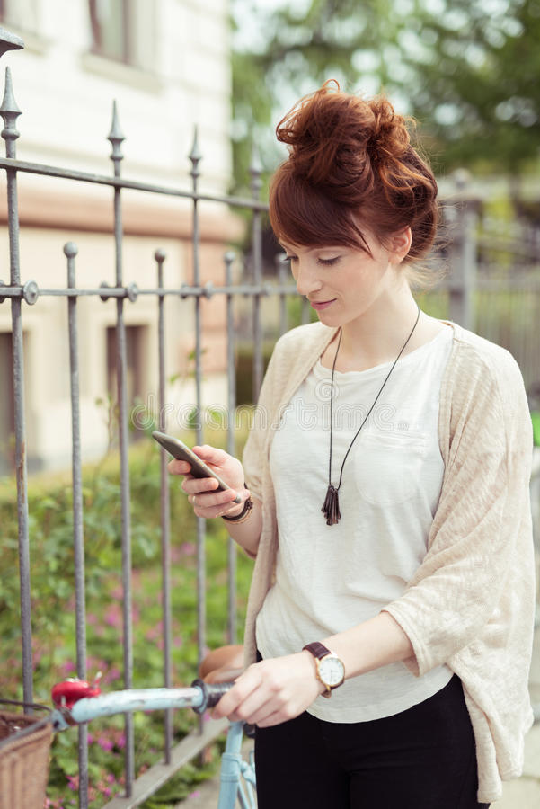 Junge Frau, die ihren Handy überprüft stockfotos