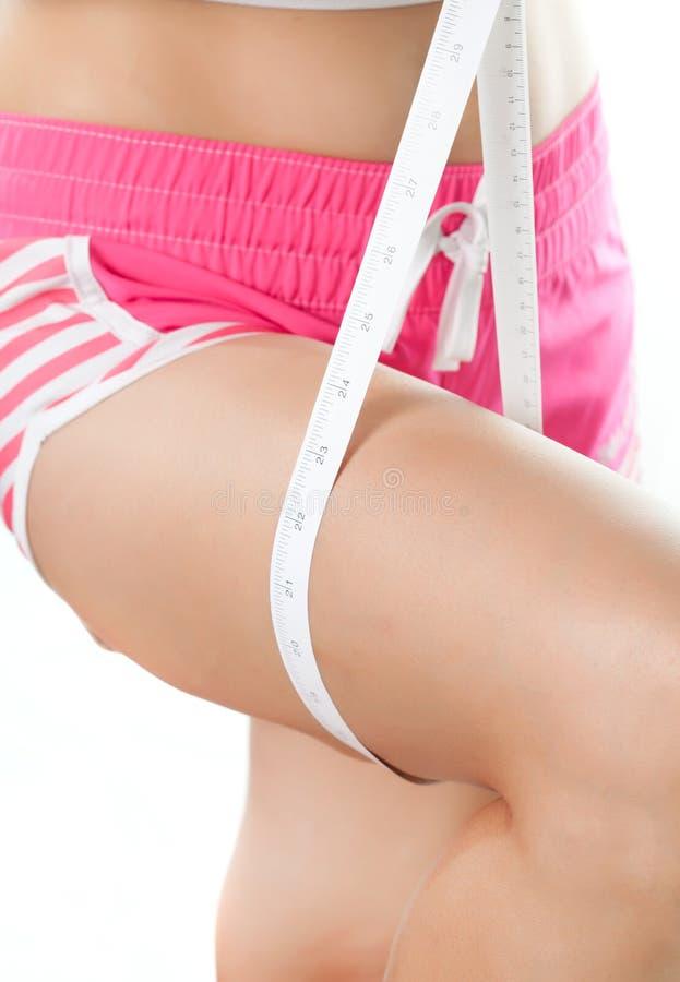 Junge Frau, die ihren Schenkel mit messendem Band misst lizenzfreie stockbilder