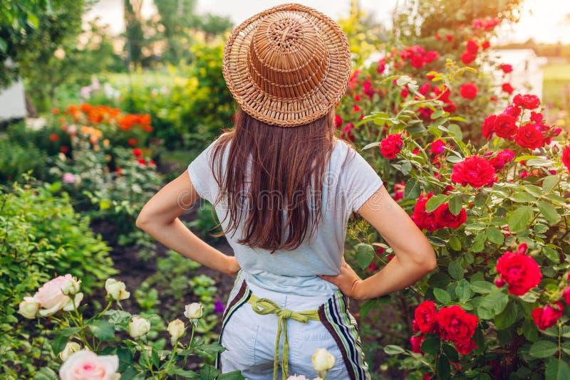Junge Frau, die ihren Sommergarten bewundert Gärtner im Schutzblech und Hut, der Blumen betrachtet lizenzfreie stockfotos