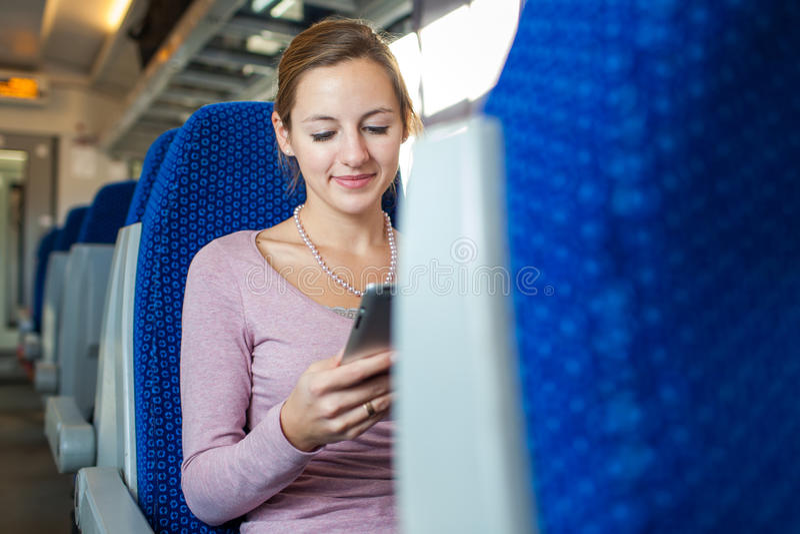 Junge Frau, die ihren Tablet-Computer beim Reisen verwendet lizenzfreie stockfotos