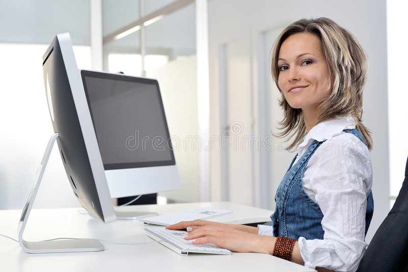 Junge Frau, die im Büro arbeitet stockfotos
