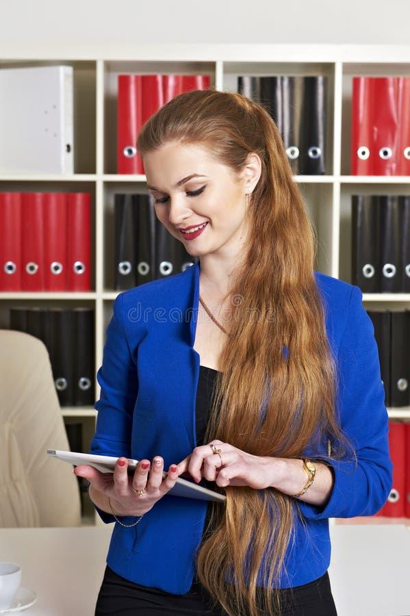 Junge Frau, die im Büro arbeitet lizenzfreie stockbilder