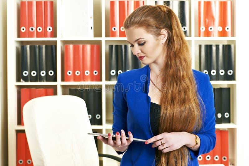 Junge Frau, die im Büro arbeitet stockfotografie