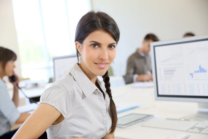 Junge Frau, die im Büro mit Kollegen im Hintergrund arbeitet stockfotografie