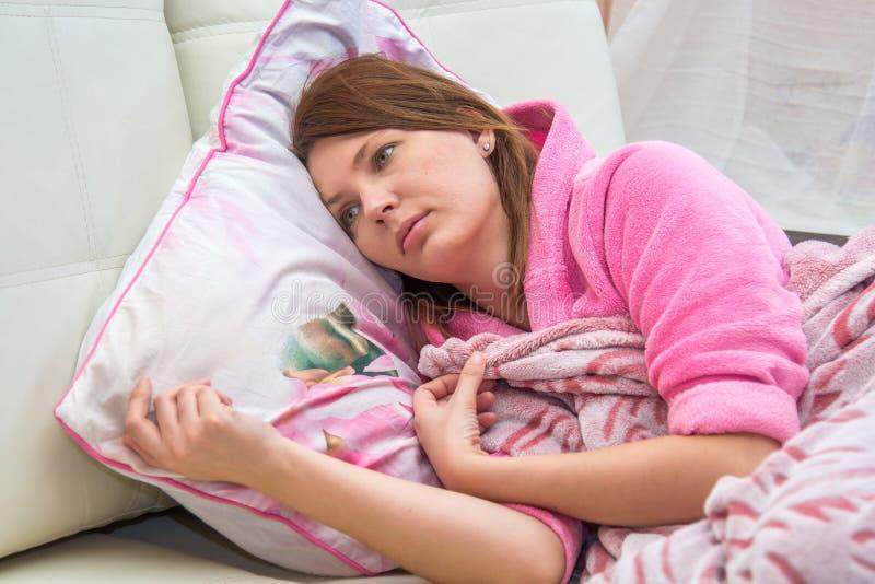 Junge Frau, die im Bett liegt lizenzfreie stockbilder
