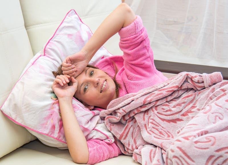 Junge Frau, die im Bett liegt lizenzfreie stockfotos