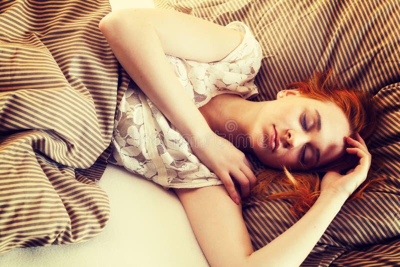 Junge Frau, die im Bett schläft lizenzfreie stockfotografie