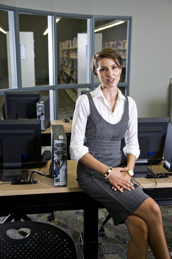 Junge Frau, die im BibliotheksComputerraum sitzt lizenzfreie stockfotos