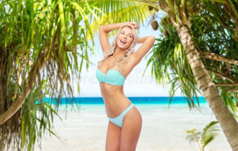 Junge Frau, die im Bikini auf Strand aufwirft stockfotografie