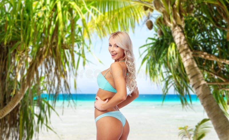 Junge Frau, die im Bikini auf Strand aufwirft stockfoto